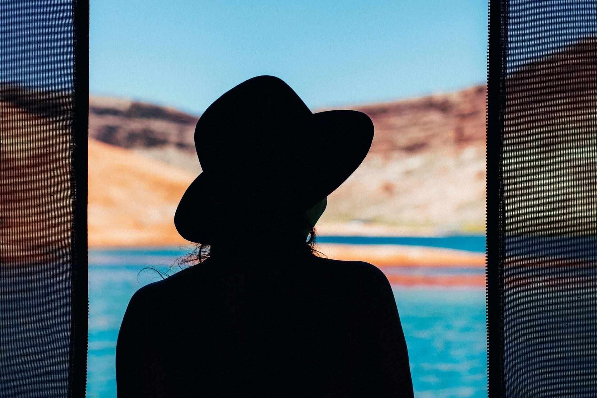 Frau mit Hut von hinten schaut aus einem offenen Fenster aufs Meer | Foto: Pixabay
