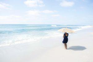 Frau im blauen Sommerkleid am Strand mit Sonnenschirm