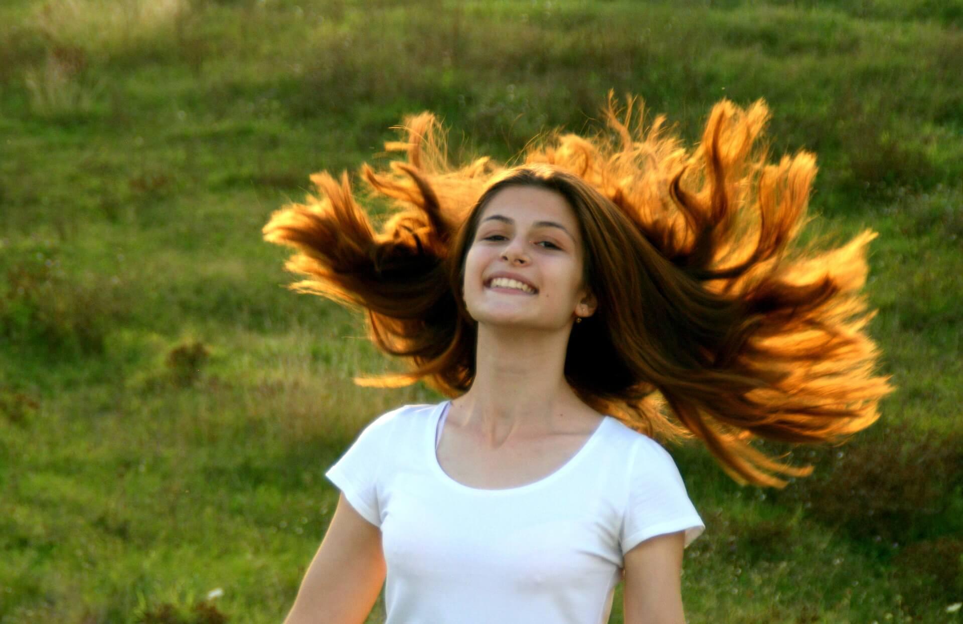 Junge Frau mit langen brünetten Haaren auf sonnenbeschiener Wiese | Foto: Pixabay