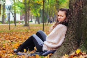 Junge Frau sitzt vor Baum auf Herbstlaub