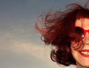Lachende Frau mit wilden roten Locken und roter Brille