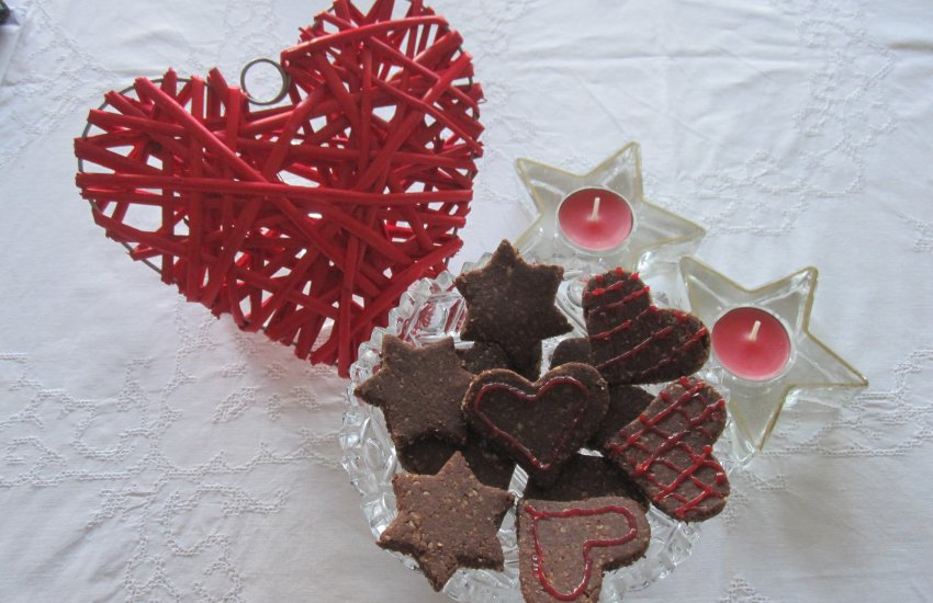 Schoko-Mandel-Plätzchen mit Deko-Herz und Kerzen