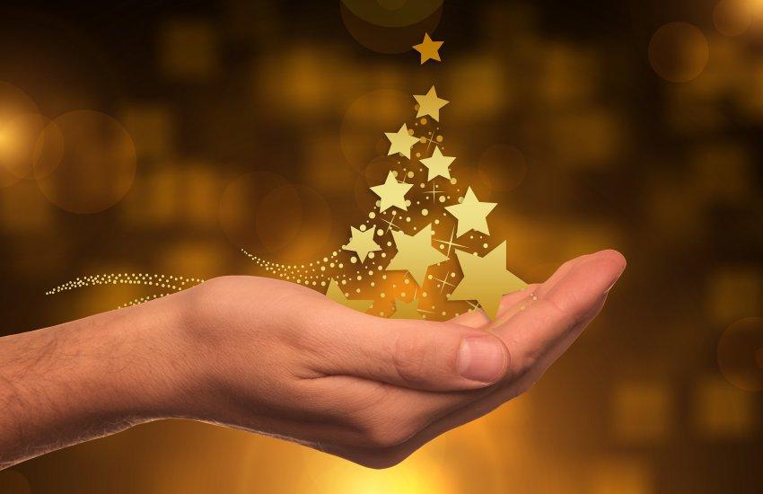 Hand hält Christbaum aus goldenen Sternen