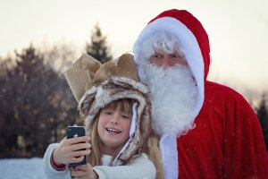 Kind macht Selfie von sich mit dem Weihnachtsmann