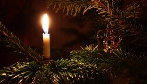Schlichte Christbaumdekoration mit Wachskerze und kupferfarbenem Schmuckelement
