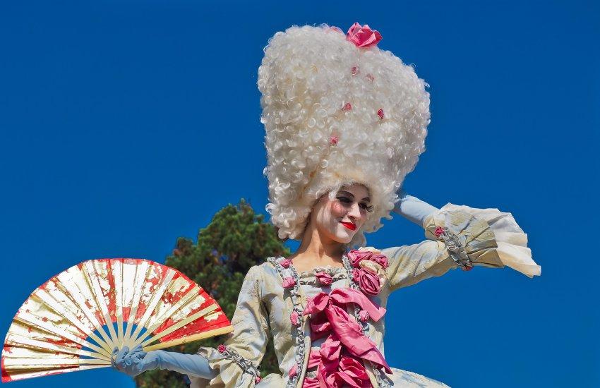 Frau in Biedermeier-Kostüm und riesiger Perücke