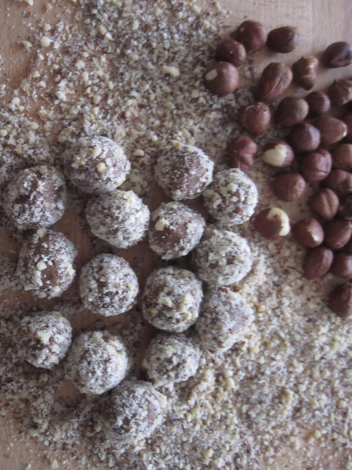 Nougatkugeln auf gemahlenen Haselnüssen und Haselnuss-Kerne