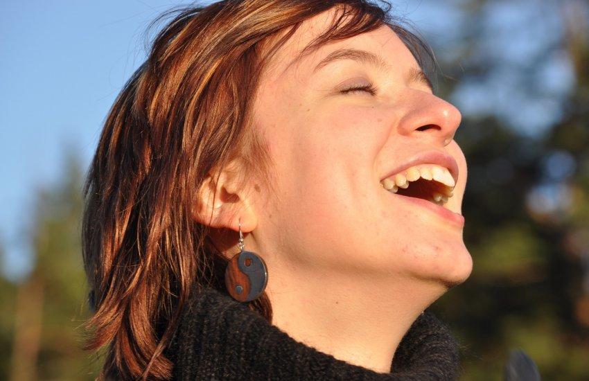 Frau mit kürzeren rotbraunen Haaren lacht